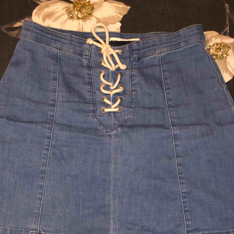 Bra skick, syns inte att den är använd. Blå jeans kjol med snöre som knyts. Kjolar.