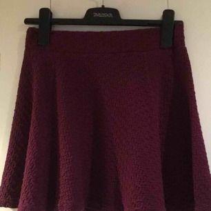 Kort mörkt lila kjol med struktur i tyget. Se sista bilden. Väldigt fint skick, storlek S