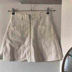 Jättefin kjol från monki, knappt använd! Sitter som en smäck med dragkedja fram och stora fickor, A-linjeformad i vit/beige färg!