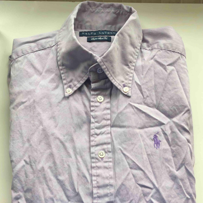 Lila Ralph lauren skjorta , säljes pga den inte kommer till användning. Kan mötas upp i Borås och Ulricehamn , även posta. . Skjortor.