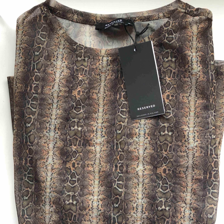 Orm mönstrad tröja. Lite genomskinlig . Aldrig använd , köpt utomlands . Kan nötas upp i Borås eller Ulricehamn , även posta. . Toppar.