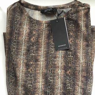 Orm mönstrad tröja. Lite genomskinlig . Aldrig använd , köpt utomlands . Kan nötas upp i Borås eller Ulricehamn , även posta.