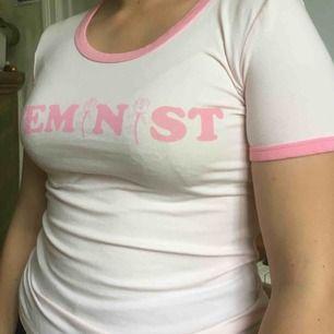 Ljusrosa t-shirt, slim fit. Tryck på bröstet: Feminist. Nyskick.