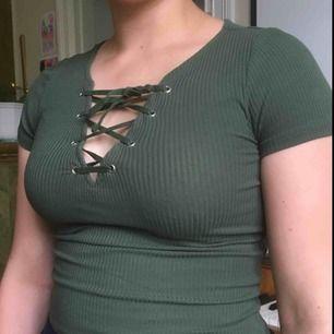 Grön tight t-shirt m kors-snörning i urringningen