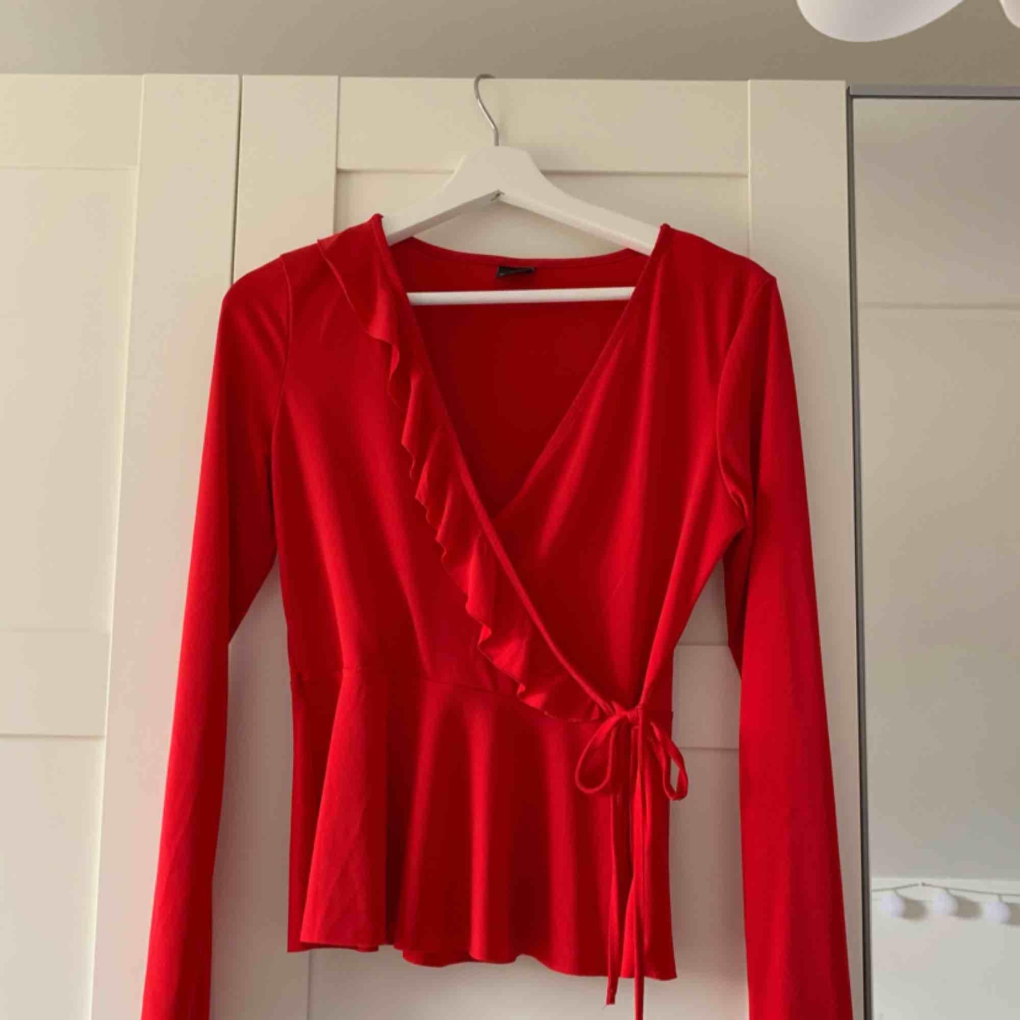 Röd blus med volang från Gina Tricot. Köparen står för frakten. Blusar.