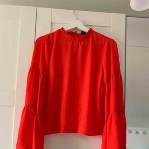 Röd blus med vida ärmar från Gina Tricot. Köparen står för frakten