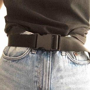 Bälte som går att reglera storleken på. Aldrig använd!