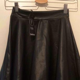 Oanvänd kjol i fejkläder från Boohoo med tags kvar. Nyskick!