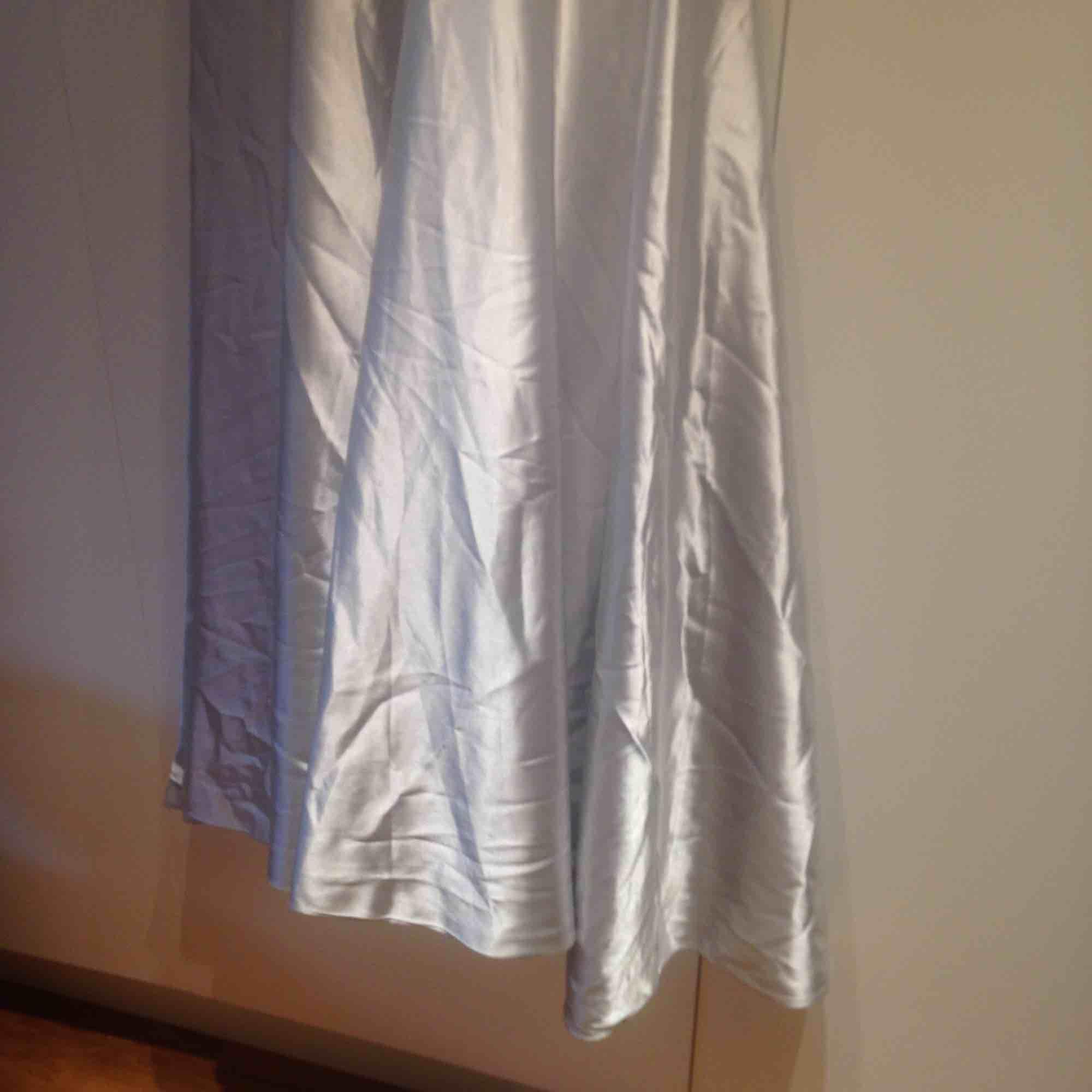 Lång balklänning i silvertyg, halterneck och långa band som hänger ner över ryggen. . Klänningar.