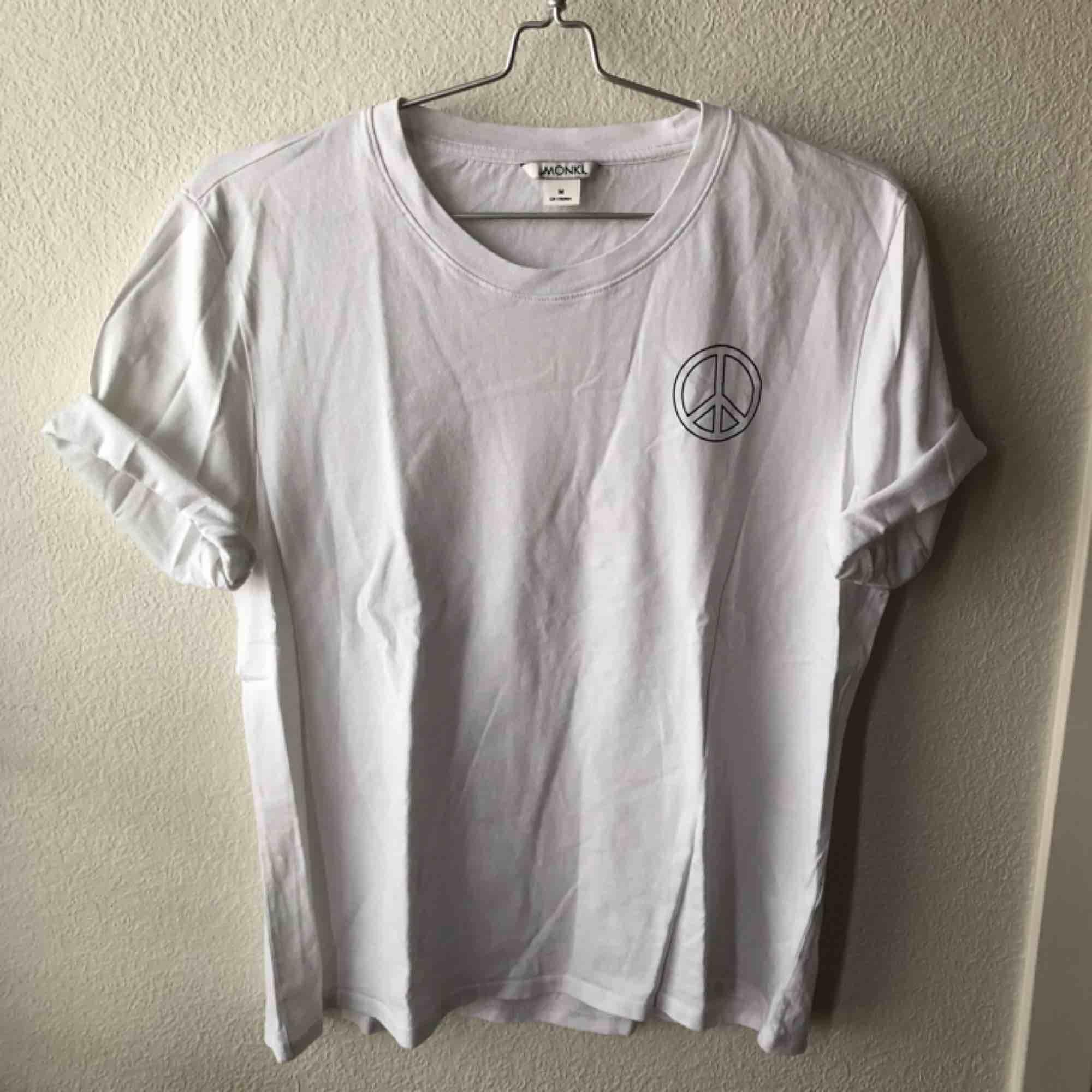 Vit t-shirt med peace-logo på ena bröstet. Från Monki. T-shirts.