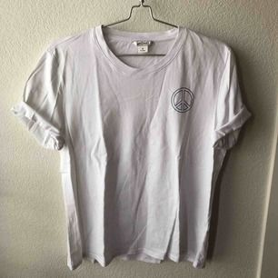 Vit t-shirt med peace-logo på ena bröstet. Från Monki