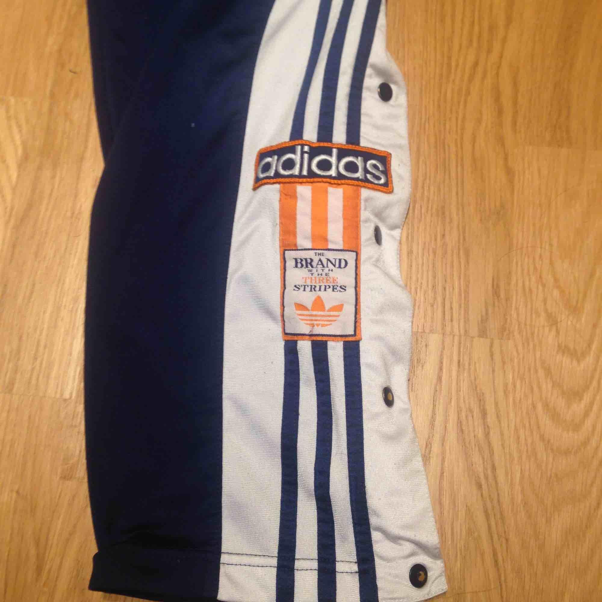 Äkta vintage 90tals adidas i använt skick med knappar längs med benen. Saknas en knapp dock. . Jeans & Byxor.