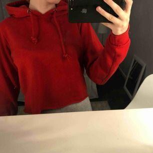 En röd cropped hoodie. Knappt kommit till användning.