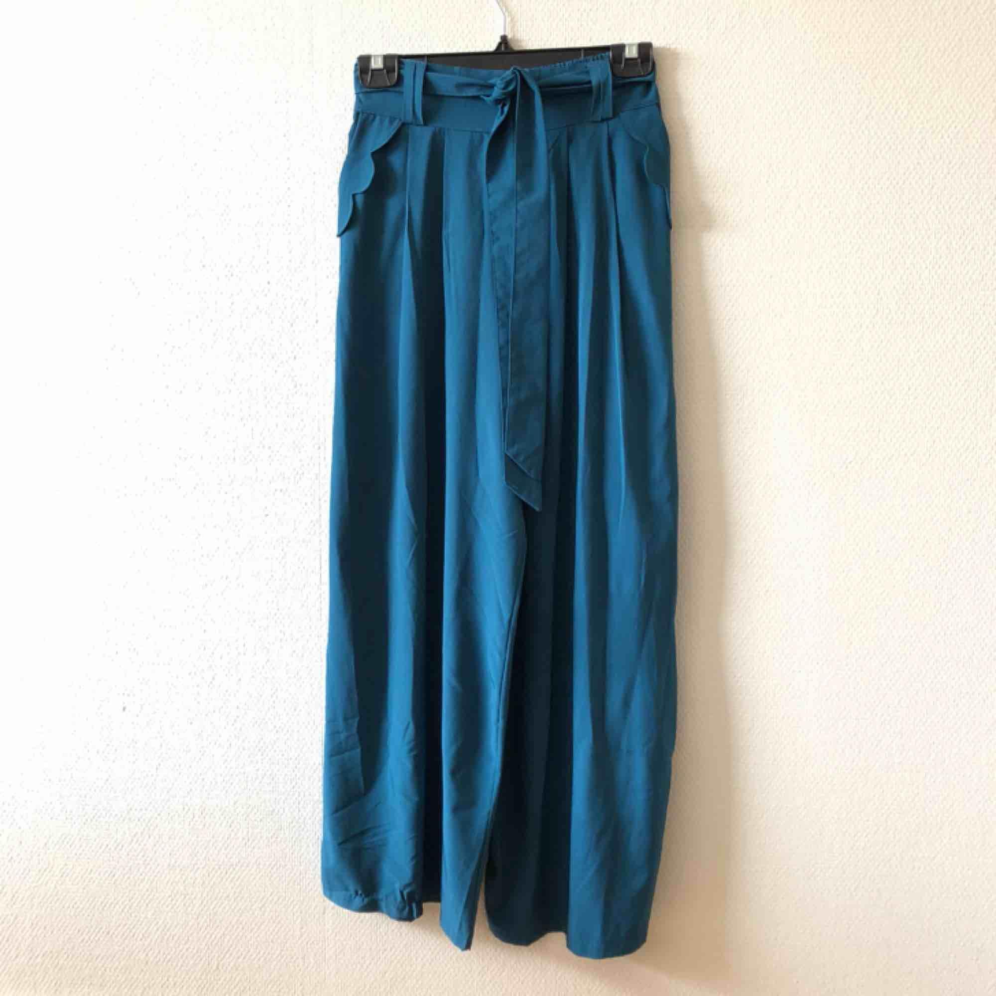 Vida & trendiga byxor med fina detaljer på fickorna   • Okänt märke • Okäng storlek, passar S-M • Högst troligen viskos men kan vara polyester • Köpta 2hand, fint skick trotts liten tråddragning • + Frakt 59kr. Jeans & Byxor.