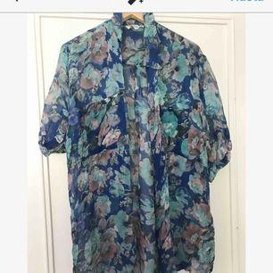 Blus/kimono i blommigt skirt material. Perfekt i sommar. Strl S-L beroende på hur man vill att den ska sitta. 150 kr pp, 100 om vi möts upp.