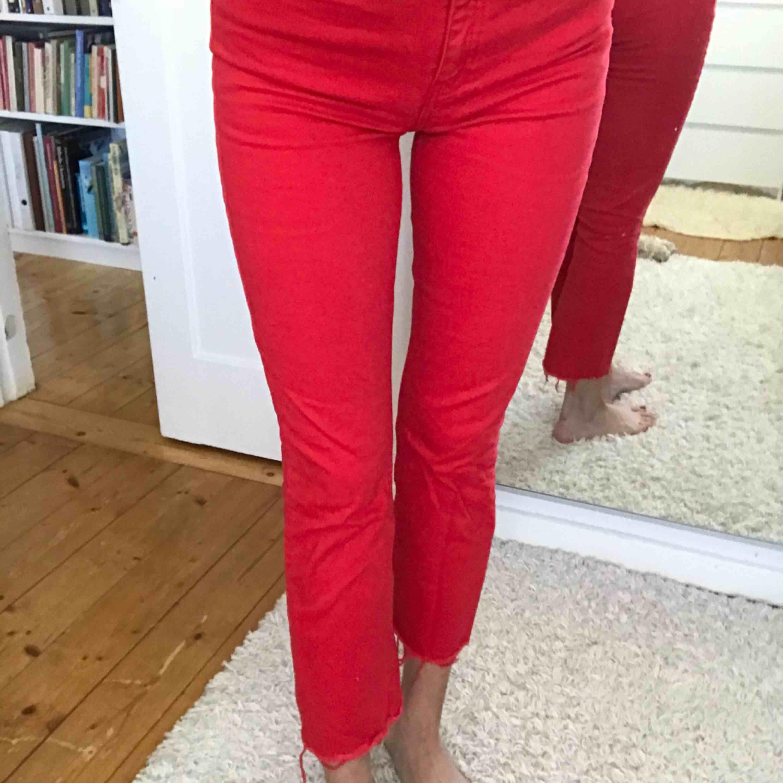 Röda jeans från Gina Tricot. Riktigt coola, rak modell, ankellånga och avklippta nedtill. Storlek 38 men skulle även funka som 36.  Frakt tillkommer.. Jeans & Byxor.