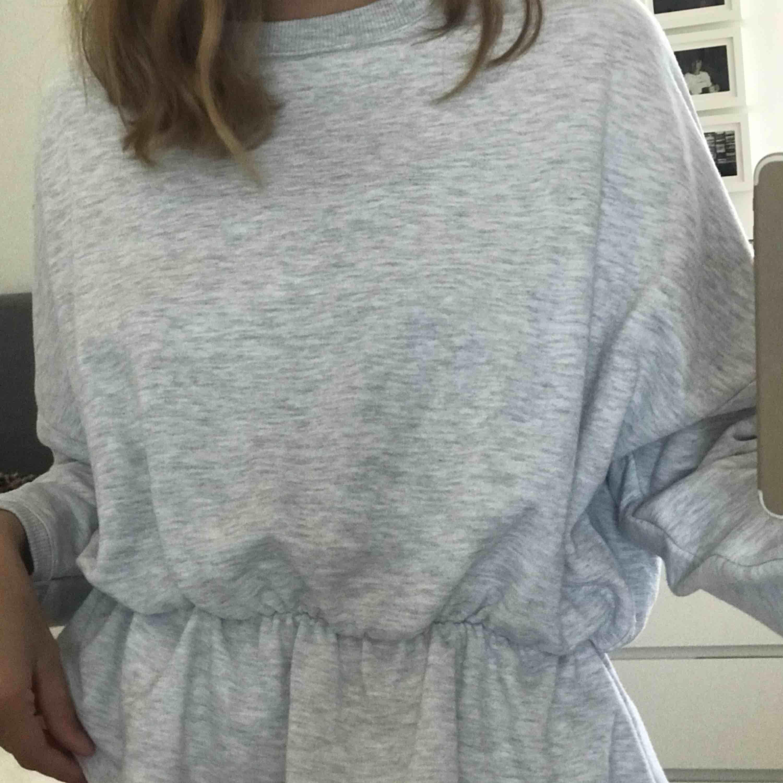 """Ljusgrå sweatshirt med lite """"kjol"""" nedtill. Supermysig och superball. Går att styla till mycket. Använd ca 2 ggr. Frakt tillkommer. Tröjor & Koftor."""