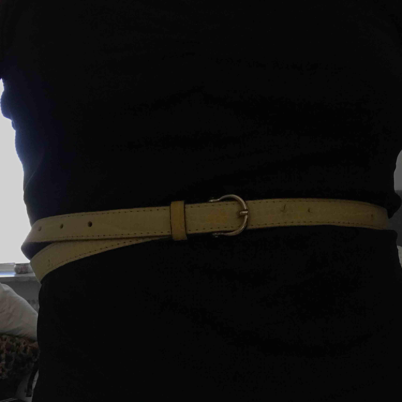 Gult skärp med guldspänne. Är typ djurmönstrat. Ganska smalt och fett tufft! . Accessoarer.