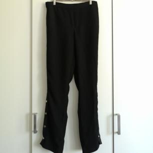 Snygga svarta byxor med knappar längs sidorna! I priset ingår frakt 😊🌻