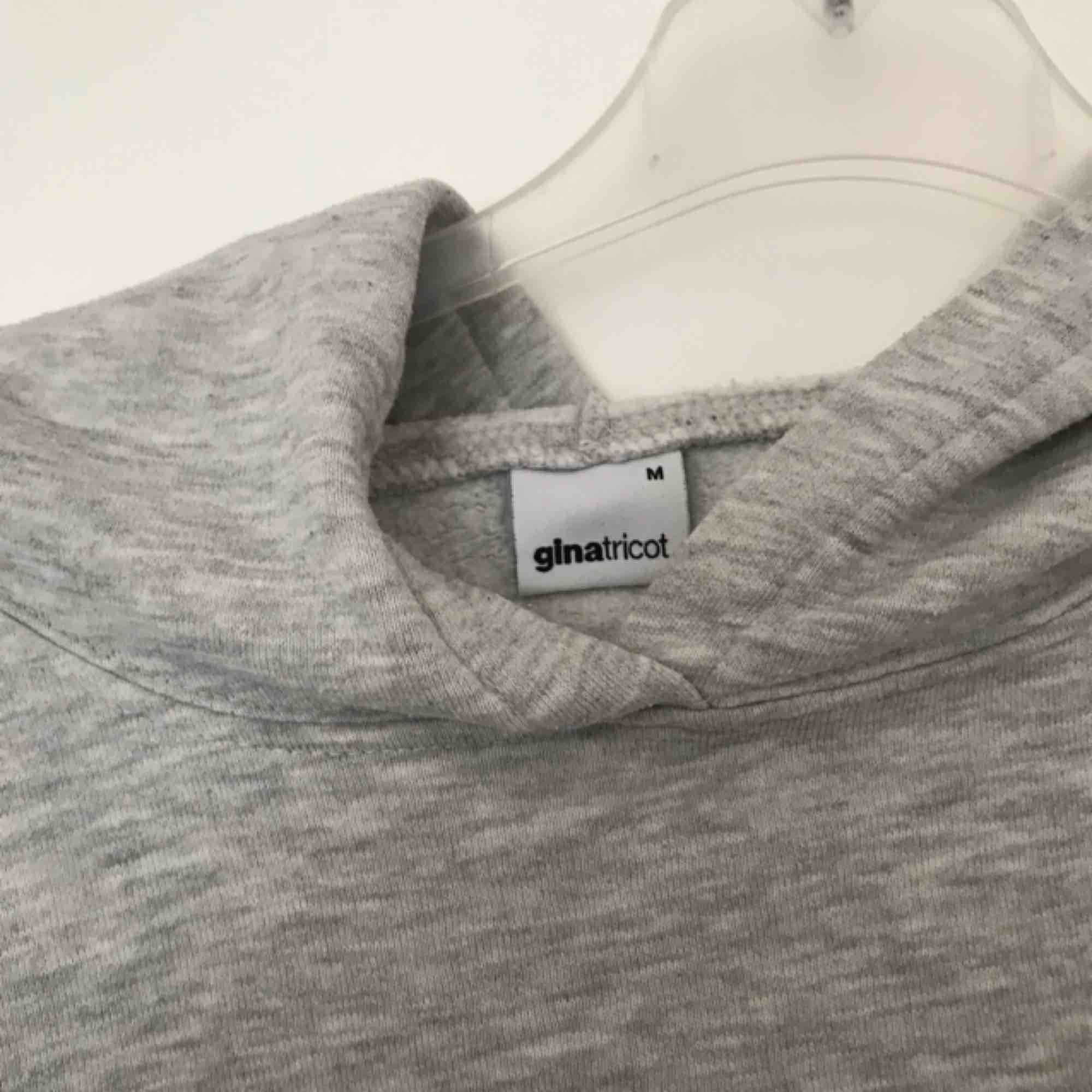 Grå hoodie utan snöre från GinaTricot! Sportinspirerad med räddar på ena ärmen och tryck på bröstet. Passar även S.. Huvtröjor & Träningströjor.