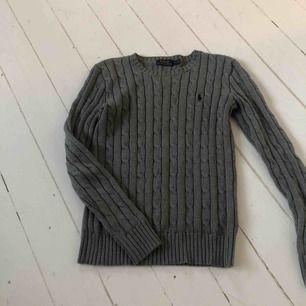 Säljer en grå kabelstickad tröja från Ralph Lauren.  Frakt tillkommer