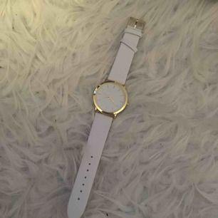 En klocka i vit och guld. Helt ny! Frakt ingår i priset.