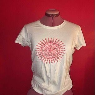 T-shirt i perfekt skick köpt utomlands med paljettbroderi på framsidan samt tryck på baksidan. Sitter snyggt på kroppen, mycket somrig.