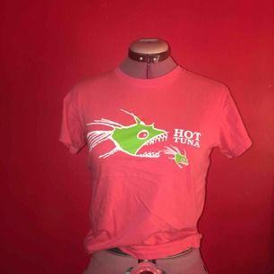 Trendig Hot Tuna T-shirt från Thailand i en liten storlek som sitter tight på kroppen. Snygg, ingen stretch i tyget så den faller snyggt. Tyvärr för smal för mig i ärmarna.