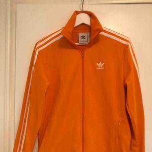 Fräsch orange Adidas tracksuit-top i nyskick!!! Använd 1 gång! Kan mötas upp, alternativt posta, frakt ligger dock på köparen. Swish