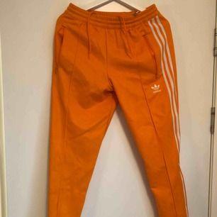 Fräscha orangea Adidas tracksuit-byxor!!! Nyskick, använda 1 gång! Kan mötas upp, alternativt posta, frakt ligger dock på köparen. Swish
