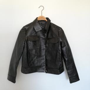 Skrynklad lack-jacka i kortare modell som stängs med knappar och  har två fickor på brösten plus vanliga dolda sidofickor. Frakt 63 kr.