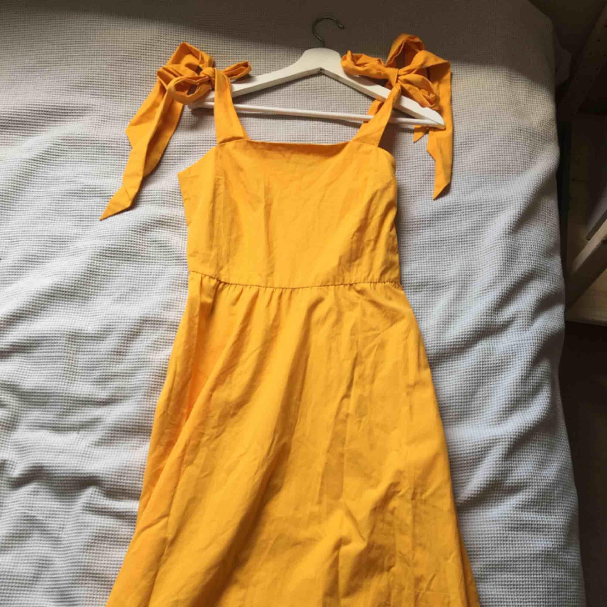 Solgul klänning från hm! Knyt över axlarna. Slutar strax efter knäna på mig som är 163 cm. Knappt använd, fint skick! . Klänningar.