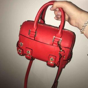 En liten röd söt väska med gulddetaljer från topshop! Använd endast ca 2 gånger och i nyskick! Väldigt rymlig och ett rött väskband medföljer!
