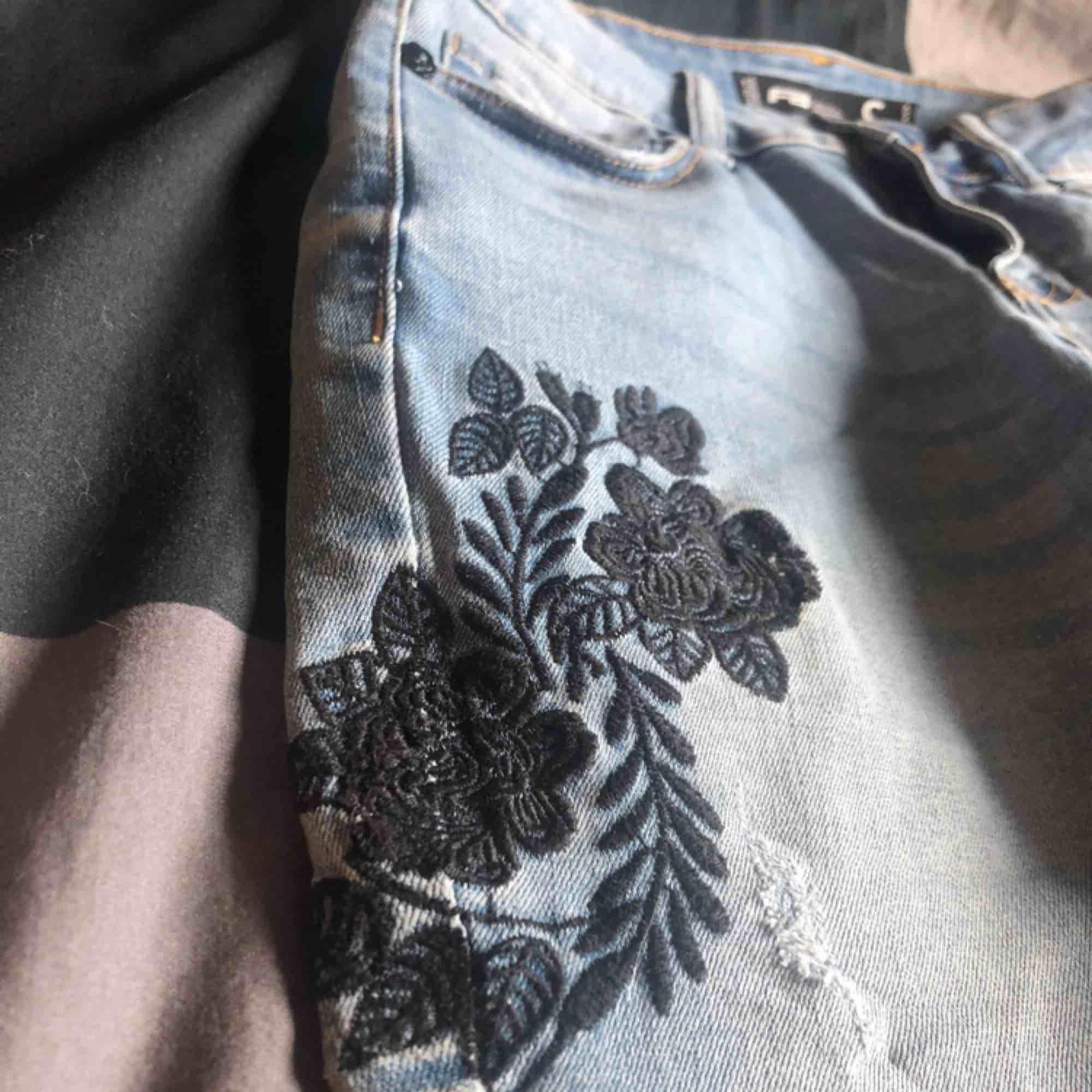 Snygga blå jeans med svart blommigt mönster. Endast använda ett fåtal gånger. Kan mätas i jönköping och kan även frakta, köparen står för frakt.. Jeans & Byxor.