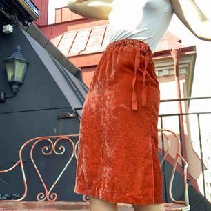 Orange MIDI-kjol i sammet och underkjol. Snörning i midja och två slits. Ej stretch.