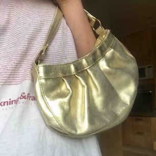 Jättesöt väska i guldsilvrigt material! Passar till typ allt, dock lite skadad (se sista bilden) Kan mötas upp, annars tillkommer 30kr i frakt!