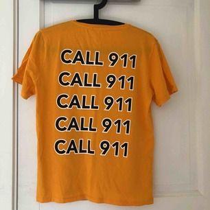 "Orange T-shirt  Tryck med text ""call 991"" på ryggen"