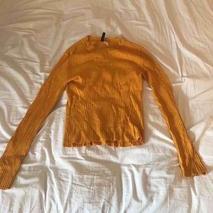 En gul tröja från h&m i strl S, väldigt stretchigt material så skulle passa upp till en också.