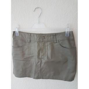 Grå skinn kjol från HM. Legat nerpackad väldigt länge så den har blivit skrynklig (se bild 3). Frakt tillkommer max 40:-