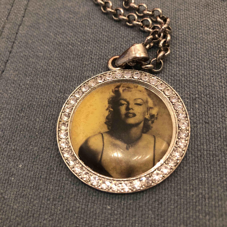 Halsband med kedja på ca 45 cm, medaljong med Marilyn Monroe och alla stenar kvar. Använt med liten slitning på baksidan där metallen är lite lätt koppar skiftande. Kan skickas mot porto annars möter upp i city Har swish. Accessoarer.