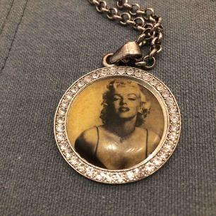 Halsband med kedja på ca 45 cm, medaljong med Marilyn Monroe och alla stenar kvar. Använt med liten slitning på baksidan där metallen är lite lätt koppar skiftande. Kan skickas mot porto annars möter upp i city Har swish
