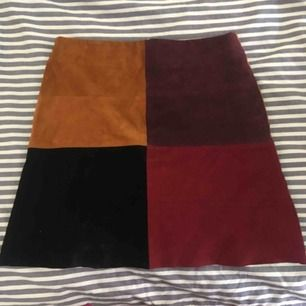 Mycket fin kjol i mocka. Vinröd, mörkröd/brun, ljusare brun och svart. Dragkedja baktill i silver. Redigt bra skick