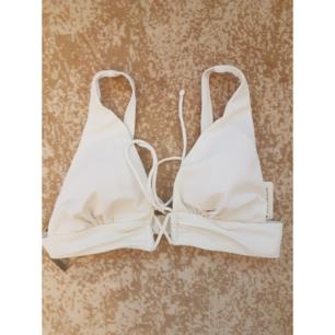 Oanvänd vit bikini topp från nelly med snören mellan brösten med tags kvar. Frakt tillkommer max 30:-