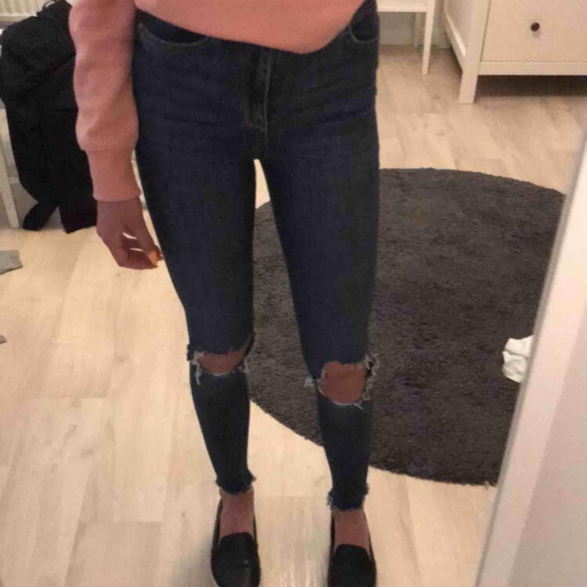 Ett par högmidjade blåa jeans med hål på knäna från Gina Tricot.Använd några gånger men är inget fel på dom.Köparen står för frakten!😊. Jeans & Byxor.