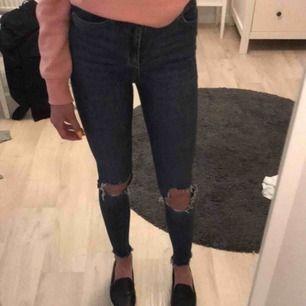 Ett par högmidjade blåa jeans med hål på knäna från Gina Tricot.Använd några gånger men är inget fel på dom.Köparen står för frakten!😊