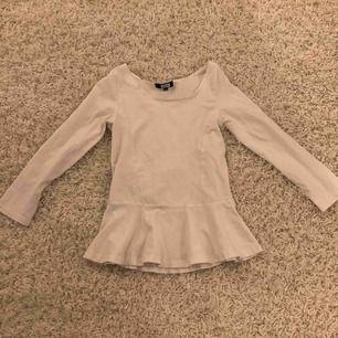 Vit långärmad tröja med volang längs ner, aldrig använd. Från bik bok storlek XS.köparen står för frakt.