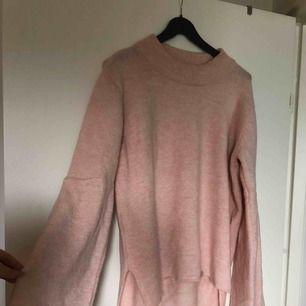 Stickad rosa tröja med klockade ärmar. Använd vid ett tillfälle