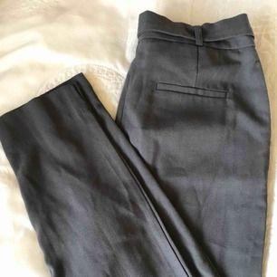 Ett par mörkgråa kostymbyxor i ett mjukt material, oanvända pga fel storlek. Köparen står för frakt
