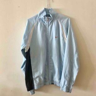 Ljusblå vintage NIKE track-jacka med orange swoosh på bröstet. Frakt tillkommer.