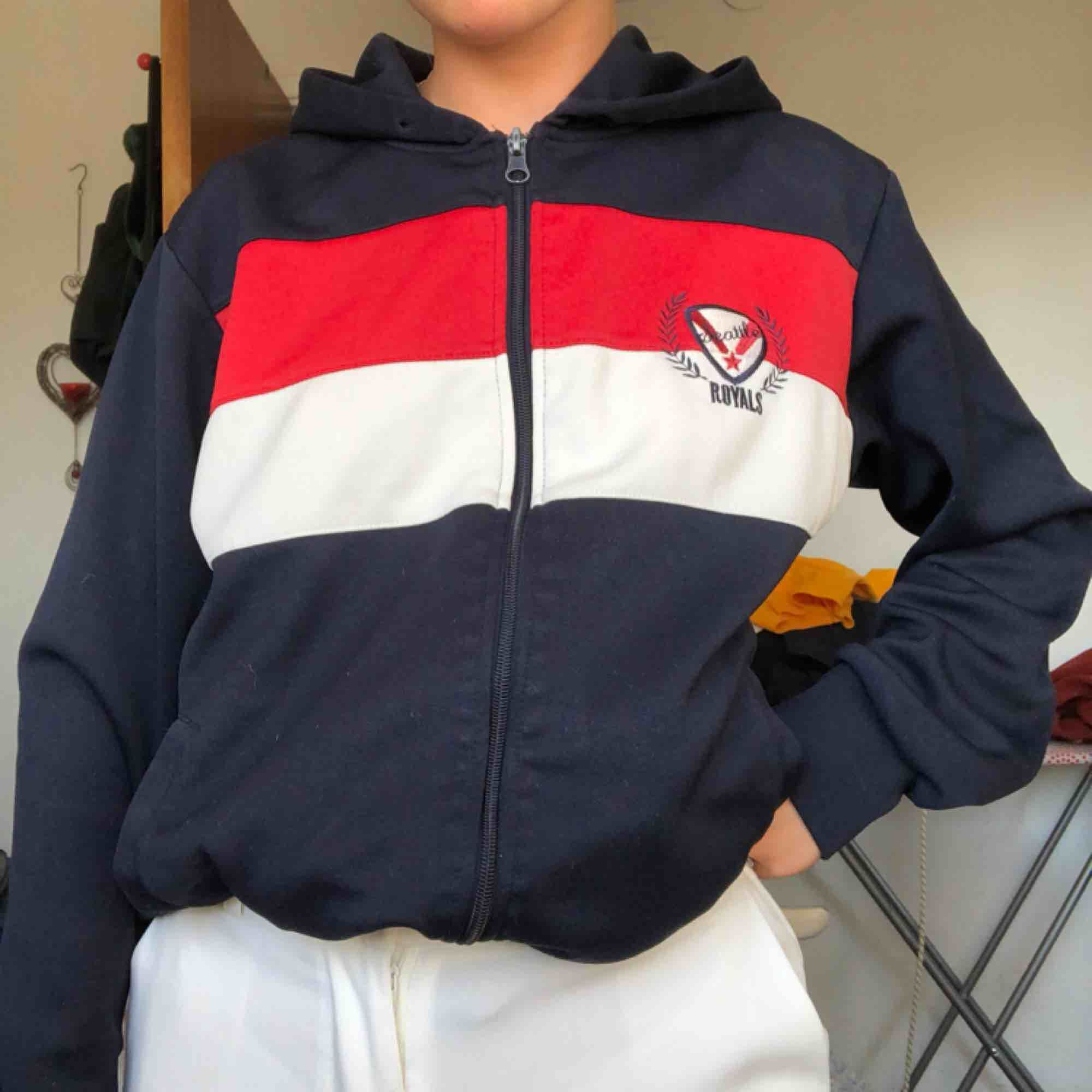Mörkblå hoodie med luva, tryck på ryggen med vita och röda detaljer. Köpt second hand. Huvtröjor & Träningströjor.